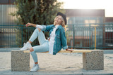 A modern, stylish girl posing while sitting on a minimal city be - 221247834