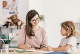 Smiling language tutor working with a little boy, drawing with crayons in his room - 221253251