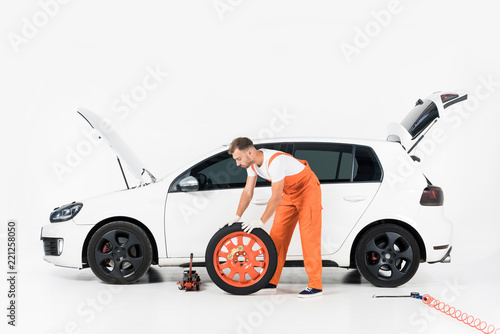 auto mechanic pushing car tire on white buy photos ap images