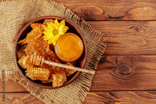 Poster Honey in jar with honey dipper on vintage wooden background