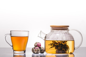 cup and teapot of chinese flowering tea with tea balls on table