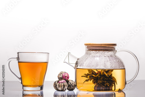 Fototapeta cup and teapot of chinese flowering tea with tea balls on table