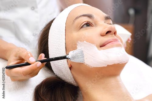 Pielęgnacja skóry, kosmetyczka nakłada maseczkę. Młoda kobieta w salonie kosmetycznym na zabiegu pielęgnacyjnym skóry twarzy.