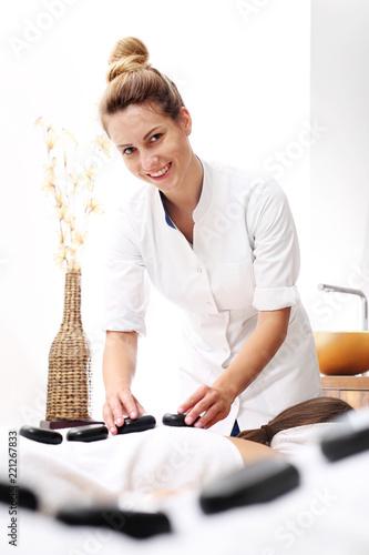Masaż kamieniami dla zakochanych. Kobieta i mężczyzna razem na masażu w gabinecie spa. - 221267833