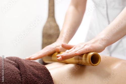 Poster Masaż bambusowy. Masażysta masuje ciało przy użyciu bambusowych kijów.