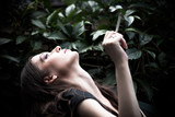 portrait of young woman with cigarette in garden closeup - 221271830