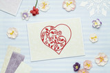 Greeting card with red heart made of paper on blue background with paper flowers. Scrapbooking, top view - 221273627