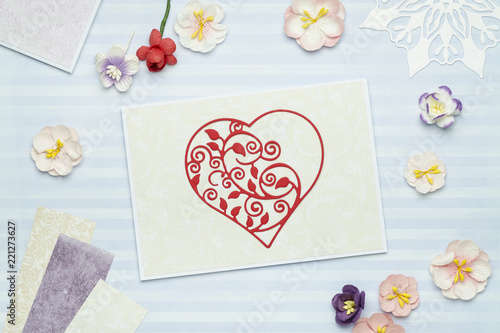 Greeting card with red heart made of paper on blue background with paper flowers. Scrapbooking, top view
