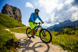 Tourist cycling in Cortina d'Ampezzo, stunning Cinque Torri and Tofana in background. Man riding MTB enduro flow trail. South Tyrol province of Italy, Dolomites. - 221274266