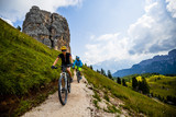 Couple cycling in Cortina d'Ampezzo, stunning Cinque Torri and Tofana in background. Woman and man riding MTB trail. South Tyrol province of Italy, Dolomites. - 221274405