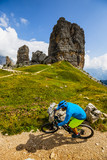 Tourist cycling in Cortina d'Ampezzo, stunning Cinque Torri and Tofana in background. Man riding MTB enduro flow trail. South Tyrol province of Italy, Dolomites. - 221274625