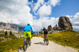 Couple cycling in Cortina d'Ampezzo, stunning Cinque Torri and Tofana in background. Woman and man riding MTB trail. South Tyrol province of Italy, Dolomites. - 221274830