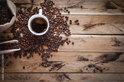 Black coffee in white cup, with coffee beans on wooden background, top view, copy space