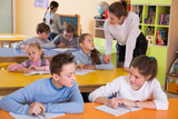 Teacher and schoolkids during lesson - 221281411