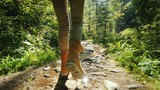 Follow shot: A man in trekking boots walks along a slippery stony path in the forest. - 221283289