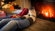Leinwanddruck Bild - Closeup image of couple wearing woolen socks relaxing by the burning fireplace on Christmas eve