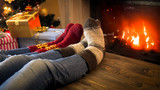 Closeup image of couple wearing woolen socks relaxing by the burning fireplace on Christmas eve
