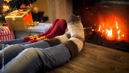 Leinwanddruck Bild Closeup image of couple wearing woolen socks relaxing by the burning fireplace on Christmas eve