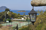 Street of the city of Turgutreis, Bodrum, Turkey. Street light. View of the tennis court and the Aegean Sea with islands. - 221291226