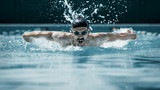The dynamic and fit swimmer in cap breathing performing the butterfly stroke at pool. The young man. The fitsport, swimmer, pool, healthy, lifestyle, competition, training, athlete, energy concept - 221291667