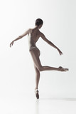 Young graceful female ballet dancer or classic ballerina dancing isolated on white studio. Caucasian model on pointe shoes - 221294013