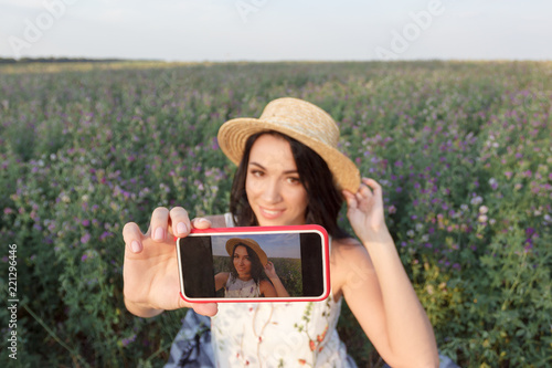 Foto Murales Beautiful young woman taking a selfie on the field of clover