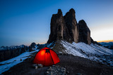 Night bivouac at Tre Cime di Lavaredo, milion star hotel under night sky, red illuminated tent on pass in Dolomites, Italy. - 221303211