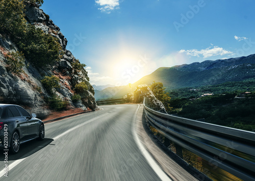 Wall mural Black car rushing along a high-speed highway in the sun.