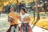 Young student couple going to college class.They walks trough university campus and laughing.Autumn. - 221306697