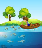 A boy on the boat watching fish - 221314834