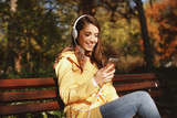 Young woman enjoys music through the headphones in the park - 221315283