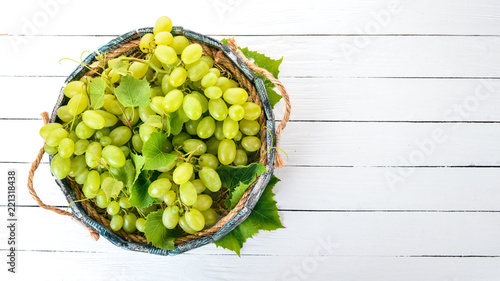 Foto Murales White Grapes in a wooden box on a white wooden table. Leaves of grapes. Top view. Free space for text.