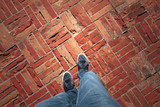 Point of view of a man walking on old damaged brick floor surface. - 221327002