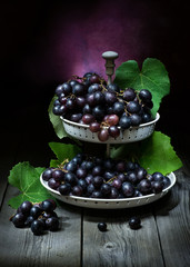 natura morta artistico con uva nera in una fruttiera