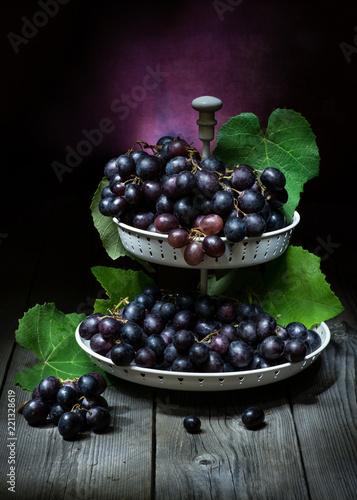 Poster natura morta artistico con uva nera in una fruttiera