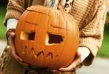 Closeup on woman showing carved Halloween pumpkin - 221329682