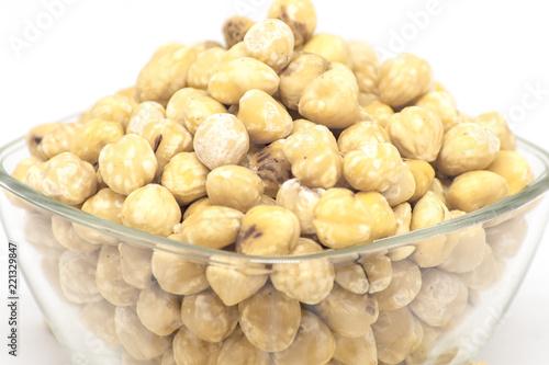 bowl with raw hazelnuts kernels on white background - 221329847