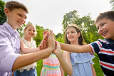 summer holidays, friendship, childhood, leisure and people concept - group of happy pre-teen kids making high five gesture in park - 221331809