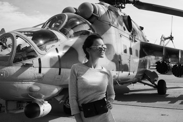 Black and white woman portrait. Attack helicopter Mi-24 on background.