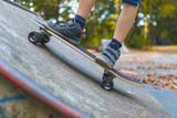 Ein Kind skatet auf einem Longboard an einer Rampe