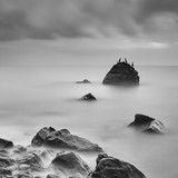 Coastal landscape with long exposure and stone on which sit cormorants - 221343619
