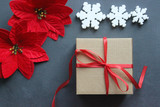 Christmas composition. Gift box with red satin ribbon, wood and snowflakes on black background.  Toys Christmas decor. Extensive series of holiday pictures with various props and backgrounds. A lot of - 221353256
