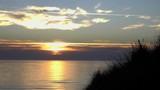 Sonnenuntergang bei stiller See auf Sylt mit Dünengras - 221360077
