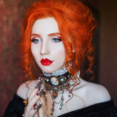 Sharp claws. Gothic halloween attire. Unusual woman pray with pale skin and red hair in black dress and necklace on neck. Unusual girl sorceress pray with vampire claws. Gothic outfit for halloween. © iiievgeniy