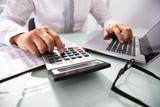 Businessman Using Laptop And Calculator - 221371098