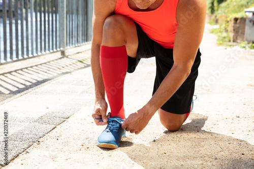 Męska atleta Wiąże Shoelace