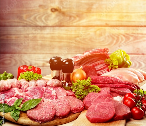 Fresh raw meat with vegetables on brown wooden table at wooden