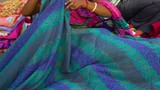 Medium shot of an Indian displaying a colourful sheet she made. - 221377479