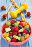 Fresh fruit salad and centimeter with dumbbells, concept of healthy lifestyle and nutrition