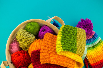 Knitting a rainbow scarf and hat Blue background © dasha_belka